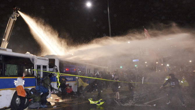 In this Saturday, April 18, 2015, photo, riot police officers spray water to disperse protesters after a rally to commemorate the first anniversary of the Sewol ferry sinking in Seoul, South Korea. South Korean police say they're questioning dozens of protesters after violence broke out at a rally denouncing the government's handling of the ferry disaster that killed more than 300 people a year ago.   (Park Dong-wook/Newsis via AP) KOREA OUT