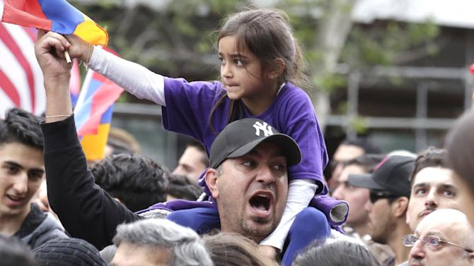 A man carrying a child on his shoulders marches with demonstrators to commemorate the 100th anniversary of mass killing of Armenians by Ottoman Turks, in Los Angeles