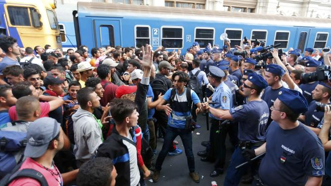 Migrants face Hungarian police in the main Eastern Railway station in Budapest