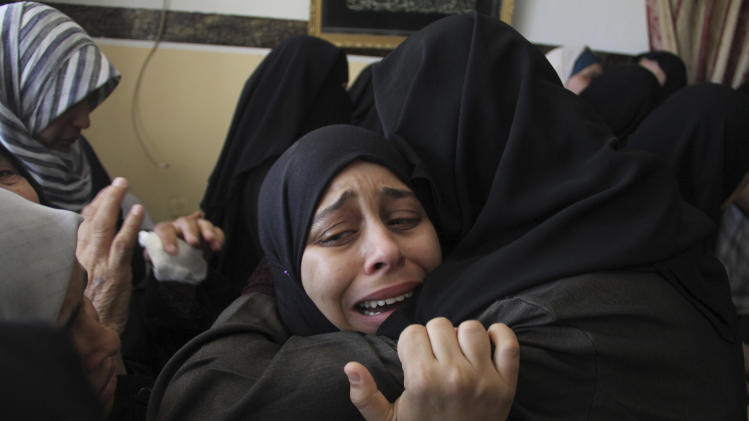 Palestinian relatives weep during the funeral of Ibrahim Hamad, an Islamic Jihad militant, at his family house during his funeral in Rafah refugee Rafah refugee camp in the southern Gaza Strip on Friday, Aug. 22, 2014. Hamad was killed in an Israeli strike while riding a motorcycle Thursday night in Rafah, according to Gaza health official Ashraf al-Kidra. (AP Photo/Hatem Ali)