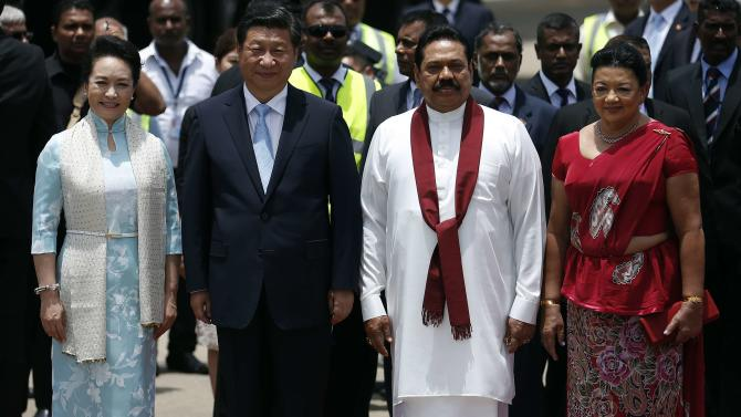 Chinese President Xi and his wife Peng pose with Sri Lanka's President Rajapaksa and his wife Rajapaksa during an official welcoming ceremony at Bandaranaike International Airport in Katunayake