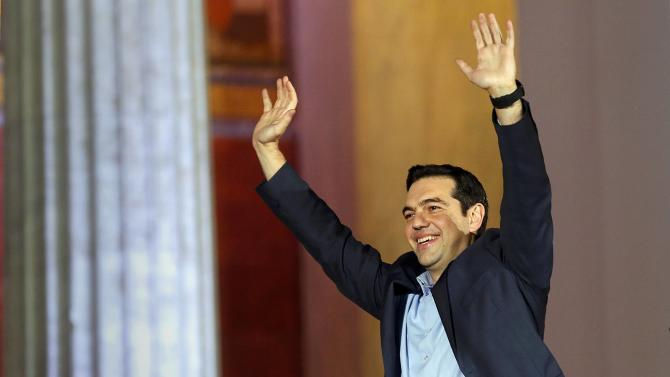Head of radical leftist Syriza party Tsipras waves after winning elections in Athens.