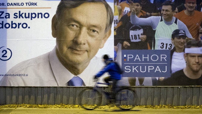 A cyclist rides past electoral posters of candidates Danilo Turk, left and Borut Pahor, right, in Ljubljana, Slovenia, Friday, Nov. 9, 2012. Three candidates are vying for the presidency this weekend in crisis-stricken Euro zone member Slovenia where deep political divisions have threatened efforts at reforms needed to avoid possible bailout. (AP Photo/Darko Bandic)