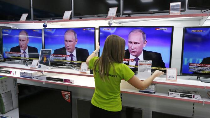 "An employee adjusts a TV set during the annual end-of-year news conference of Russian President Putin at the ""Pozitronika"" electronic store in Divnogorsk"