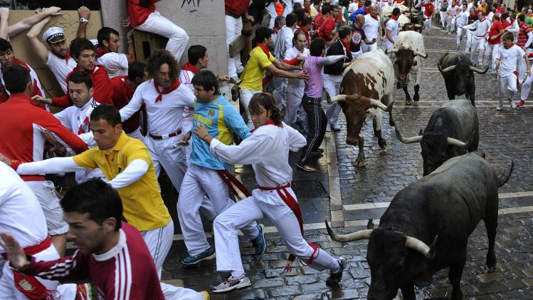 Runners sprint in front of Adolfo Martin fighting bulls on Estafeta corner during the seventh running of the bulls of the San Fermin festival in Pamplona