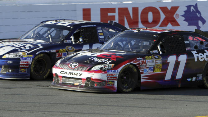Denny Hamlin (11) competes against Jimmie Johnson during the final restart in the NASCAR Sprint Cup Series auto race at New Hampshire Motor Speedway, Sunday, Sept. 23, 2012, in Loudon, N.H. Hamlin won the race, and Johnson finished second. (AP Photo/Jim Cole)