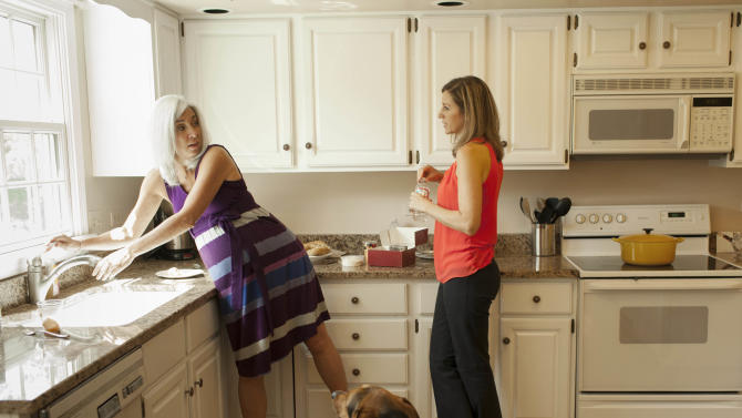 Emily Jordan, right, chats with her pregnant mother Cindy Reutzel on Sunday, Aug. 19, 2012 in Naperville, Ill. After Jordan underwent a radical hysterectomy, she and her husband took up an offer from Reutzel to act as their surrogate. (AP Photo/Sitthixay Ditthavong)