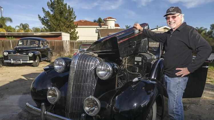 "In this photo taken Monday, Jan. 7, 2013, car collector, Garvin Kotzin, 63, poses with his 1936 Oldsmobile convertible with a tan ragtop featured in the ""Gangster Squad"" film, in Los Angeles. At left, a bullet-nosed 1947 Ford sedan. To bring the story of mobster Mickey Cohen's reign over post-war Los Angeles to life, the director of  ""Gangster Squad"" employed Sean Penn, Josh Brolin, Ryan Gosling and more than 100 irreplaceable vintage American cars. (AP Photo/Damian Dovarganes)"