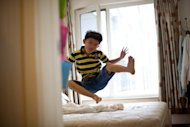 Eight-year-old Zhang Hongwu plays on his parents&#39; bed following a session of home schooling at the apartment where he lives with his father Zhang Qiaofeng in Beijing in July. Zhang, one of a small but growing number of Chinese parents who are turning their backs on the country&#39;s rigidly exam-oriented state-run school system, felt he had no choice but to give up his career to home school his son