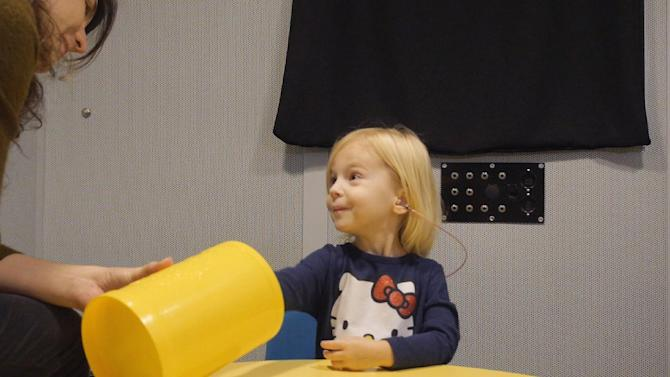 """In this images from video provided by University of North Carolina at Chapel Hill, a toddler participates in a speech perception experiment in a laboratory at the University of North Carolina in Chapel Hill, N.C.. The toddler was conditioned to put a block in the bucket whenever she heard the """"target"""" word. From the cacophony of day care to the buzz of TV and electronic toys, noise is more distracting to a child's brain than an adult's, and new research shows it can hinder how youngsters learn. In fact, one of the worst offenders when a tot's trying to listen is other voices babbling in the background, researchers said Saturday at a meeting of the American Association for the Advancement of Science. (Emily Buss/University of North Carolina at Chapel Hill via AP)"""