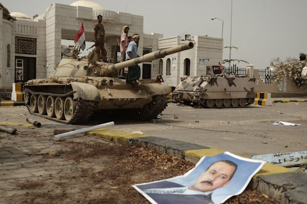 A poster of Yemen's former President Ali Abdullah Saleh lies on the ground as army soldiers and tribesmen loyal to the army gather on a tank in front of the local authority compound in the city of Zin