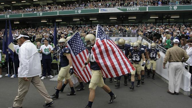 Navy  head coach Ken Niumatalolo, left,  leads his team onto the field before an NCAA college football game against Notre Dame in Dublin, Ireland, Saturday, Sept. 1, 2012.  (AP Photo/Peter Morrison)