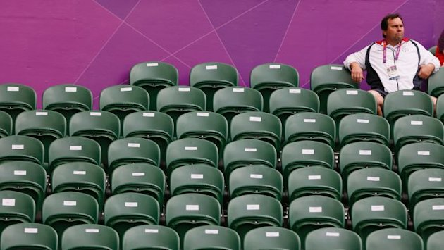 Tennis spectator sits amid empty seats at the 2012 London Olympic Games