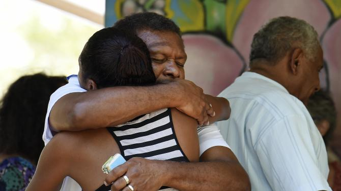 Attendees hug at church service for eight children killed in Cairns suburb of Manoora