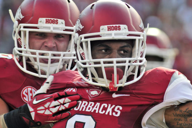 In this photo taken Aug. 31, 2013, Arkansas running back Alex Collins, right, and linebacker Austin Jones celebrate after a play during the second half of an NCAA college football game in Fayetteville