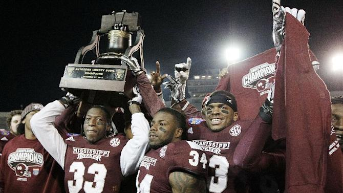 Mississippi State players Kivon Coman (33), Josh Robinson (34) and Michael Hodges, right, celebrate with the trophy after beating Rice in the Liberty Bowl NCAA college football game Tuesday, Dec. 31, 2013, in Memphis, Tenn. Mississippi State won 44-7. (AP Photo/Mark Humphrey)