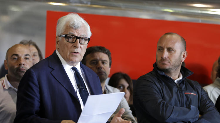 Luna Rossa Challenge owner Patrizio Bertelli, left, calls for new safety measures as his captain, Max Sirena, right, listens during a news conference at the America's Cup team's base Friday, May 17, 2013, in Alameda Calif. The owner of the Italian entry in the America's Cup says his boat will compete this summer, but sought new safety measures after the death of a sailor on a training run last week. Bertelli announced at a press conference at his team's Alameda headquarters Friday that he wanted races canceled if winds on the San Francisco Bay were deemed too dangerous. (AP Photo/Eric Risberg)