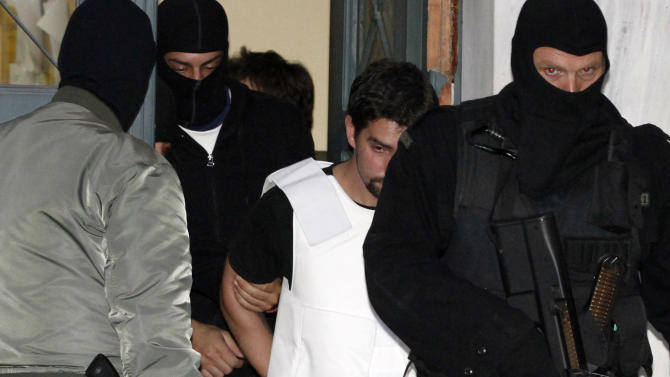 ** RETRANSMISSION TO ADD IDENTIFICATION **  Anti terrorism Police escort mail bomb suspect Gerasimos Tsakalos to a public prosecutor's office  in Athens on Tuesday Nov. 2, 2010. Eight embassies in Athens were the intended targets of mail bomb attacks Monday and Tuesday. French President Nicholas Sarkozy was also targeted with a package that was intercepted.  (AP Photo/Petros Giannakouris)