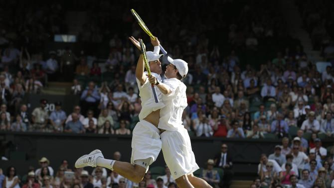 Bob Bryan and Mike Bryan of the United States celebrate after beating Ivan Dodig of Croatia and Marcelo Melo Brazil to win the Men's doubles final match at the All England Lawn Tennis Championships in Wimbledon, London, Saturday, July 6, 2013. (AP Photo/Anja Niedringhaus)