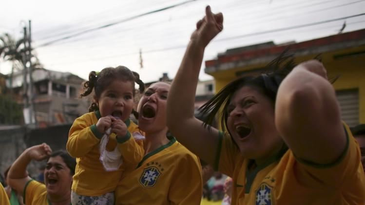 Brazilian soccer fans celebrate their teams goal against Cameroon near Sao Paulo's World Cup stadium in Sao Paulo