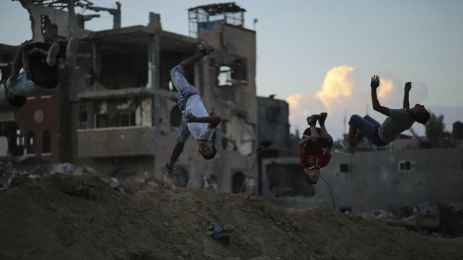 Palestinian youths practise their Parkour skills near the ruins of houses in the Shejaia neighborhood east of Gaza City