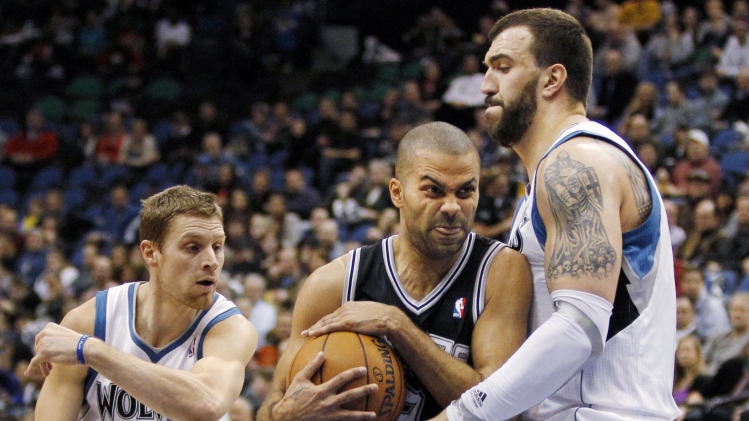 San Antonio Spurs guard Tony Parker, center, of France, drives around Minnesota Timberwolves center Nikola Pekovic, of Montenegro, right, and guard Luke Ridnour (13) during the first half of an NBA basketball game Wednesday, Feb. 6, 2013, in Minneapolis. (AP Photo/Genevieve Ross)