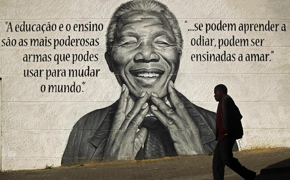 "A man walks past a mural of the former South African President Nelson Mandela that reads in Portuguese: ""Eduction and teaching are the most powerful weapons which you can use to change the world"", left, and ""if people can learn to hate, they can be taught to love"", in Loures, on the outskirts of Lisbon, Portugal, Friday, Dec. 6, 2013. Mandela passed away Thursday night after a long illness. He was 95. As word of Mandela's death spread, current and former presidents, athletes and entertainers, and people around the world spoke about the life and legacy of the former South African leader. (AP Photo/Francisco Seco)"