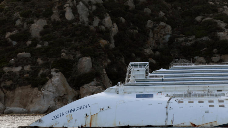 A view of the partially sunk Costa Concordia wreckage next to the Giglio Island, Italy,  Sunday, Oct. 14, 2012. The first hearing of the trial for the Jan. 13, 2012  tragedy, where 32 people died after the luxury cruise Costa Concordia was forced to evacuate some 4,200 passengers after it hit a rock while passing too close to the Giglio Island, is taking place in Grosseto Monday Oct. 15, 2012. Captain Schettino, who was blamed for both the accident and for leaving the ship before the passengers, is scheduled to attend the hearing. (AP Photo/Gregorio Borgia)