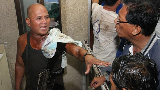 A Filipino trooper explains how he survived as their ship sank in Cebu, central Philippines late Friday Aug. 16, 2013. Passenger ferry MV Thomas Aquinas with nearly 700 people aboard sank near the central Philippine port of Cebu on Friday night after colliding with a cargo vessel, and a survivor said he saw bodies in the sea. (AP Photo/Chester Baldicantos)