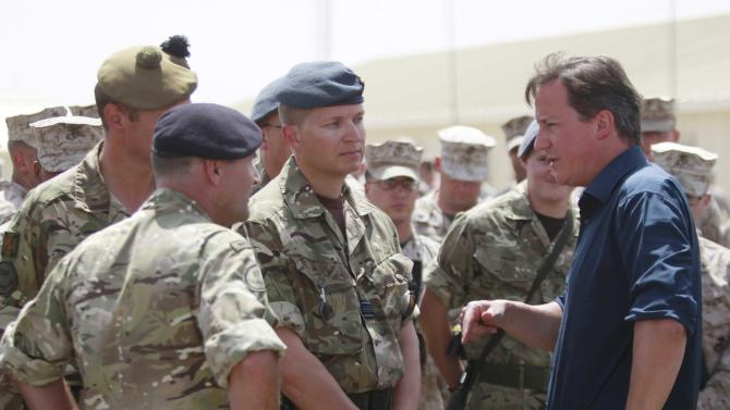 Britain's Prime Minister David Cameron talks with British troops during a visit to Camp Bastion, outside Lashkar Gah, the provincial capital of Helmand province in south Afghanistan, Monday, July 4, 2011. (AP Photo/Lefteris Pitarakis, pool)