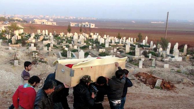 In this citizen journalism image taken on Sunday, Jan. 20, 2013 and provided by Edlib News Network, ENN, which has been authenticated based on its contents and other AP reporting, relatives and mourners carry the coffin of a Free Syrian Army fighter, Fouad Mohammed, who was injured during the battle of Taftanaz air base earlier this month, during his funeral, at Binsh village in Idlib province, north Syria. (AP Photo/Edlib News Network ENN)