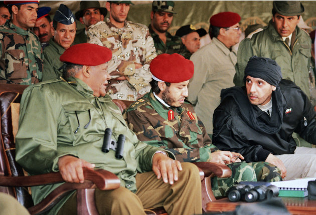 In this undated photo made available Sunday, Sept. 25, 2011, al-Saadi Gadhafi, center, and Hannibal Gadhafi, right, sons of Libyan leader Moammar Gadhafi, are seen in the audience at a military exerci