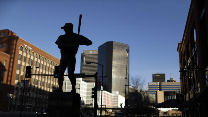 FILE - This Jan. 20, 2013 file photo shows a statue of former St. Louis Cardinals baseball player Stan Musial outside Busch Stadium in St. Louis. All the baseball teams are based in major U.S. cities and many of the stadiums are situated in bustling downtown areas with engrossing things to do and savory places to eat when you aren't attending a game. These attractions should help the cause of baseball fans trying to recruit a spouse or other traveling teammates who may not appreciate the sublime pleasures of the game. (AP Photo/Jeff Roberson)
