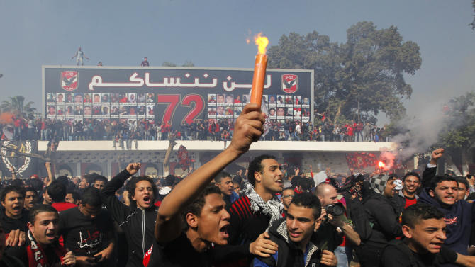 """Egyptian soccer fans of Al-Ahly club celebrate in front of their club in Cairo, Egypt, Saturday, March 9, 2013 An Egyptian court confirmed death sentences against 21 people for their role in a deadly 2012 soccer riot that killed more than 70 people in the city of Port Said. Banner at background showing some pictures of the victims with Arabic that reads, """"we will never forget you."""" (AP Photo/Amr Nabil)"""