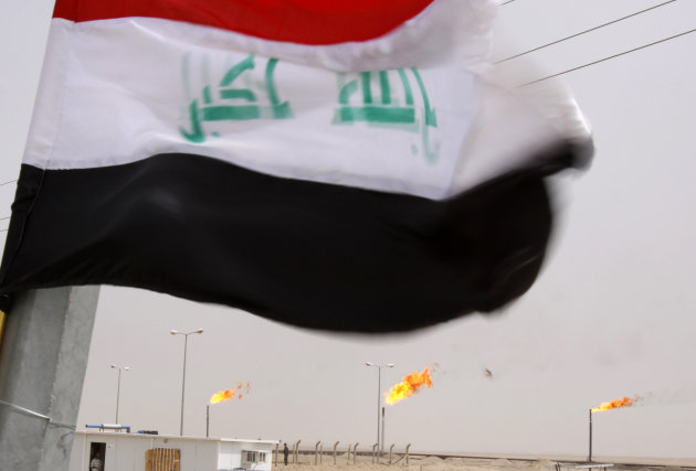 FILE - In this Saturday, June 4, 2011 file photo, the Iraqi national flag flies over a newly inaugurated gas processing facility at Tuba oil field in the southern oil-rich province of Basra, 550 kilom