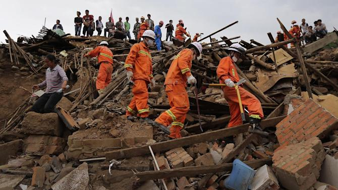 Rescuers and a villager walk past rubbles from destroyed houses following a massive earthquake in the town of Longtoushan in Ludian County in southwest China's Yunnan Province Tuesday, Aug. 5, 2014. Rescuers raced Tuesday to evacuate villages near rising lakes formed by landslides, complicating relief efforts following a strong earthquake in southern China that killed more than 300 people and has left thousands homeless. (AP Photo/Andy Wong)
