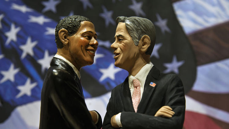 Two statuettes depicting President Barack Obama, left, and Republican rival Mitt Romney are backdropped by the Stars and Stripes in a shop which sells Christmas nativity figures in Naples, Italy, Monday, Oct. 22, 2012, hours ahead of their third and final presidential debate in Boca Raton, Florida. (AP Photo/Salvatore Laporta)