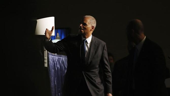 U.S. Attorney General Eric Holder gestures as he exits after speaking at the annual meeting of the American Bar Association in San Francisco