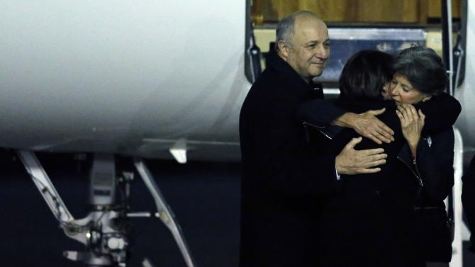 Former hostage Claudia Priest hugs her daughter next to French Foreign Minister Laurent Fabius at her arrival at a military airport, near Paris
