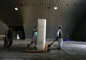 Afghan election commission workers move ballot boxes and election material in a warehouse in Kabul