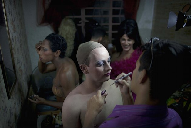 In this May 15, 2013 photo, Gilberto Diez, right, applies makeup to Dayan Sanchez, 25, a gay transvestite artist known as &quot;Venus&quot; in preparation for a drag show at the Fashion Bar Havana, in Havana, C
