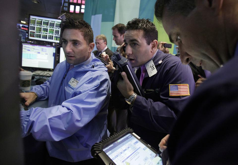 Trader Michael Liloia, center, works on the floor of the New York Stock Exchange Friday, Oct. 5, 2012. Stocks are rising in early trading on Wall Street after the government reported that the U.S. unemployment rate fell below 8 percent for the first time in almost four years. (AP Photo/Richard Drew)