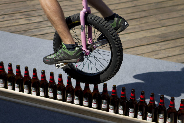 German unicycle rider Lutz Eichholz rides over beer bottles as he attempts to break his existing Guinness World record Monday, Sept. 26, 2011 in Tel Aviv, Israel. Eichholz rode his unicycle 8.93 meter