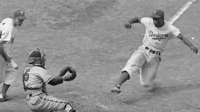 "FILE - This Aug. 22, 1948 file photo shows Brooklyn Dodgers Jackie Robinson, right, stealing home plate as Boston Braves' catcher Bill Salkeld is thrown off-balance on the throw to the plate during the fifth inning at Ebbets Field in New York. With the new movie ""42"" bringing the Jackie Robinson story to a whole new generation, fans young and old may be interested in seeing some of the places in Brooklyn connected to the Dodger who integrated Major League Baseball. (AP Photo/File)"