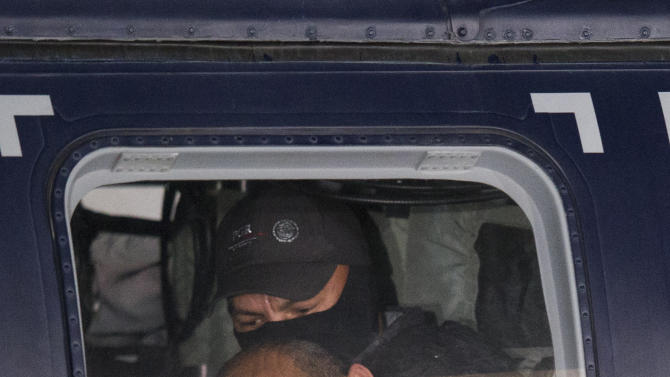 """In this Feb. 27, 2015 photo, Servando """"La Tuta"""" Gomez,"""" leader of the Knights Templar cartel, looks out the window of a federal police helicopter at the Attorney General's Office hangarin Mexico City.Gomez, a former school teacher who became one of Mexico's most-wanted drug lords as head of the Knights Templar cartel, was captured early Friday by federal police, according to Mexican officials. (AP Photo/Rebecca Blackwell)"""