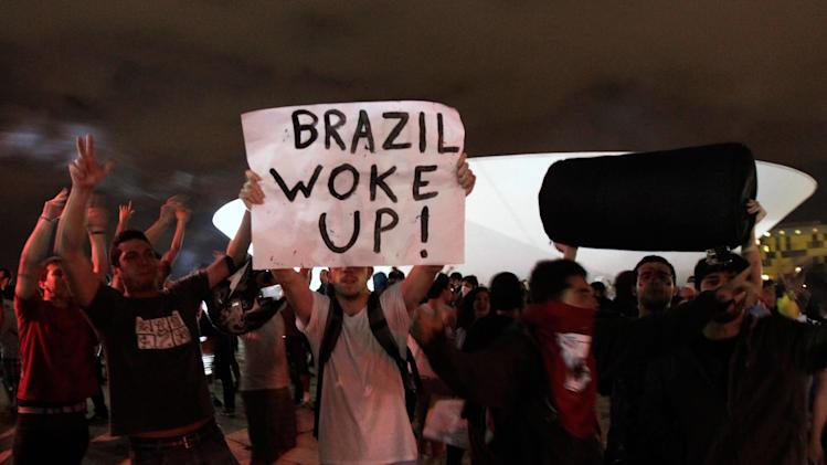 Demonstrators shout slogans during a protest in front of the  Brazilian National Congress in Brasilia, Brazil, Monday, June 17, 2013. Protesters massed in at least seven Brazilian cities Monday for another round of demonstrations voicing disgruntlement about life in the country, raising questions about security during big events like the current Confederations Cup and a papal visit next month. (AP Photo/Eraldo Peres)