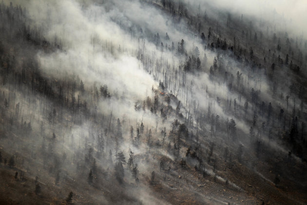 A sudden wind shift draws smoke back over the top of Sheep Mountain as the Squirrel Creek fire spreads Tuesday, July 3, 2012 near Woods Landing, Wyo. (AP Photo/Laramie Boomerang, Andy Carpenean)