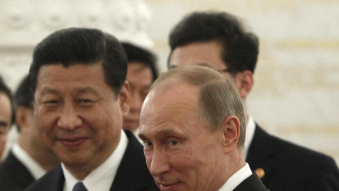 Russian President Vladimir Putin, right, gestures as Chinese President Xi Jinping looks on during their meeting in the Grand Kremlin Palace in Moscow, Russia, Friday, March 22, 2013. Vladimir Putin rolled out a grandiose reception Friday for China's new president, who has chosen Moscow as his first foreign destination, underlining close ties between the former Cold War-era rivals that are anchored in energy interests and a shared aspiration to curtail the U.S. influence. (AP Photo/Sergei Karpukhin, Pool)