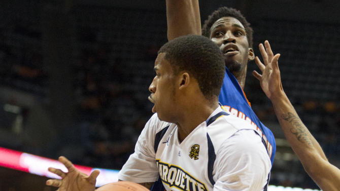 Marquette's Vander Blue drives into the lane and looks to make a pass as Savannah State's Arnold Louis defends during the first half of an NCAA college basketball game, Saturday, Dec. 15, 2012, in Milwaukee. (AP Photo/Tom Lynn)