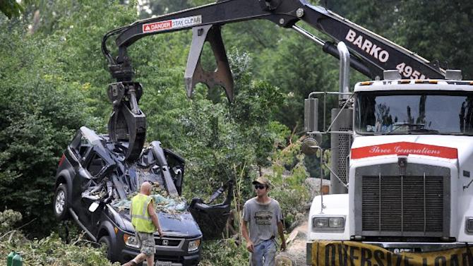 In the process of cutting up and removing an Oak tree blocking Inglewood Road, Wednesday, July 4, 2012, in Lynchburg, Va., a crane lifts the crushed Honda Element that Amy Scott and her son, Cooper, were inside of Friday night as the tree fell on top of them. Both were treated for minor injuries and are back at home. (AP Photo/The News & Advance, Parker Michels-Boyce)